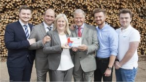 Group photo of people standing in front of log pile holding an award