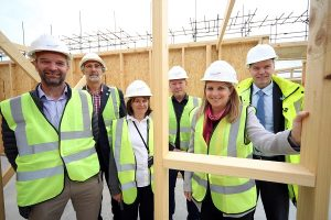 Group of 6 people on a building site with timber frame and OSB.