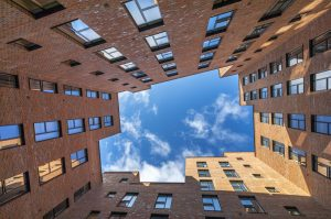 Image from bottom of buildings looking up to blue sky above