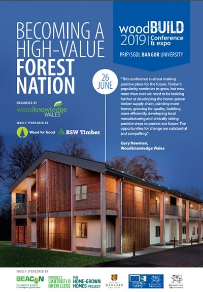 Front page of flyer for WoodBUILD 2019 blue back ground with wooden building lit up